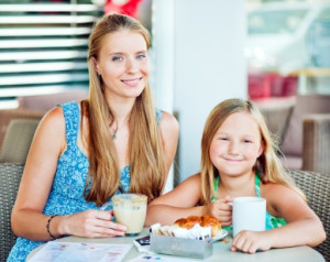 mother and daughter have a warm drink together